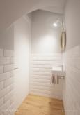 Mała, biała łazienka pod schodami