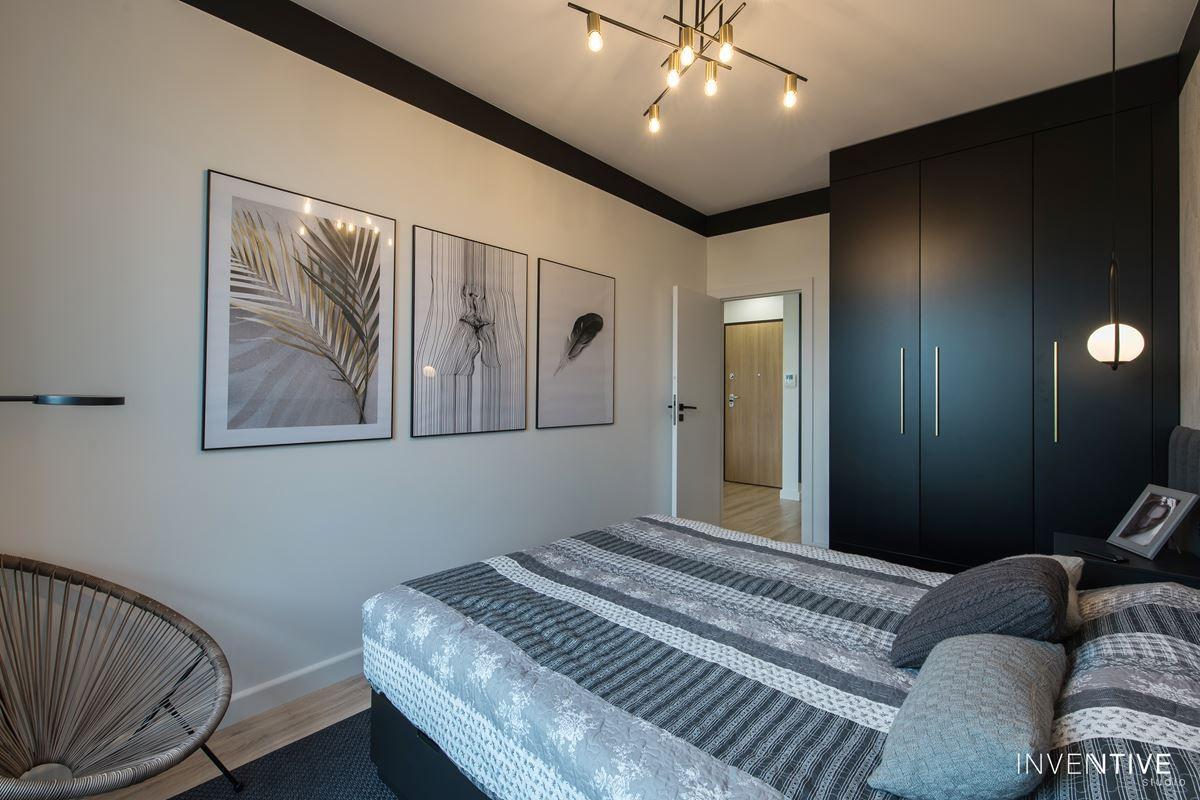 Projekt sypialni ze stylowym, rattanowym fotelem