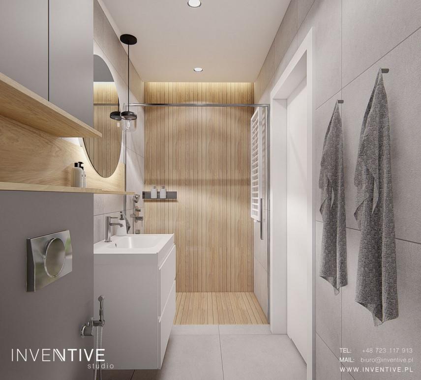 Łazienka z drewnianą ścianą pod prysznicem