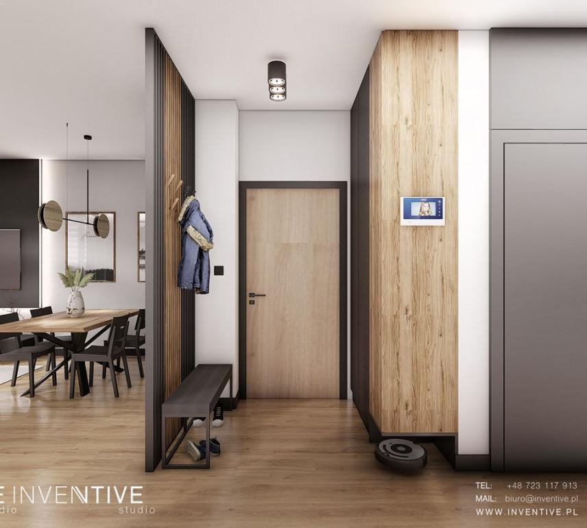 Wejście do mieszkania oddzielone drewnianą ścianą od salonu