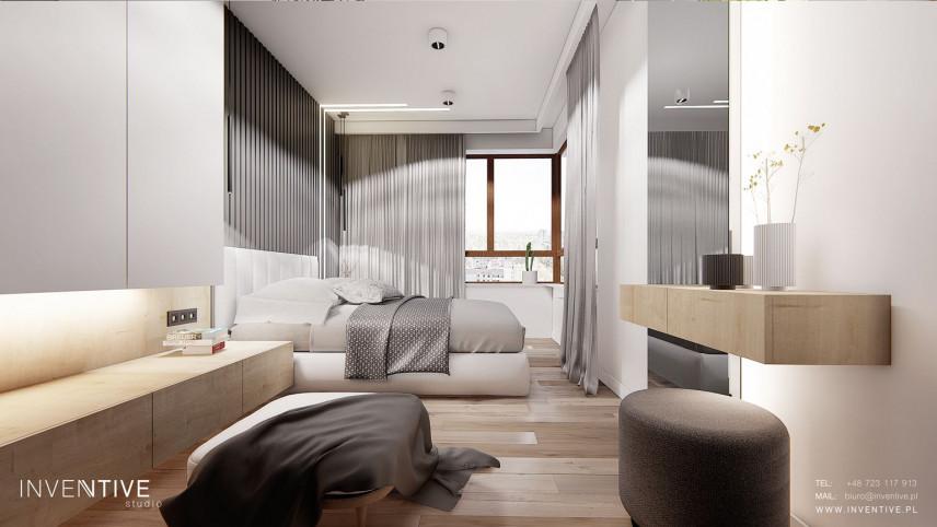 Sypialnia z białą szafką zamontowaną do ściany