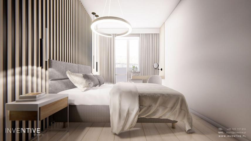 Sypialnia z jasnymi panelami i okrągłą lampą wiszącą