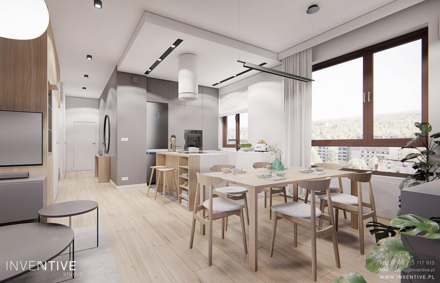 Jadalnia z drewnianym stołem połączona z kuchnią
