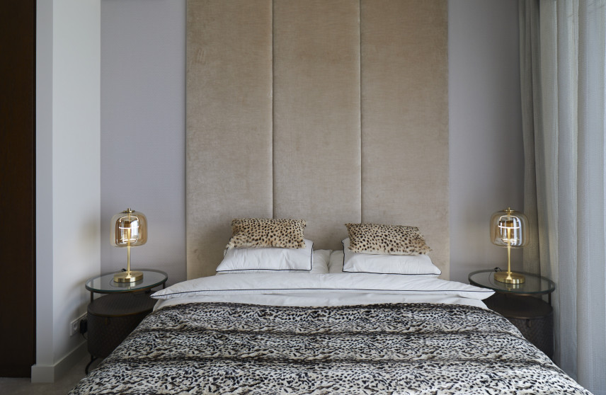 Sypialnia w stylu glamour ze  ścianą z elementami tapicerowanymi