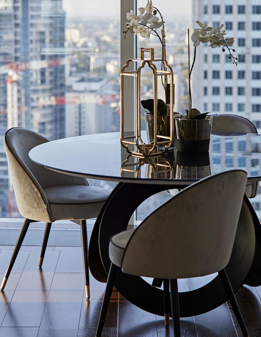 Salon z okrągłym stolikiem i tapicerowanymi krzesłami