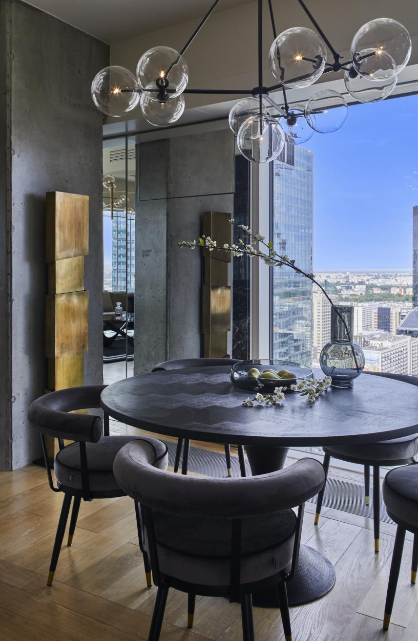 Aranżacja salonu z okrągłym, czarnym stołem