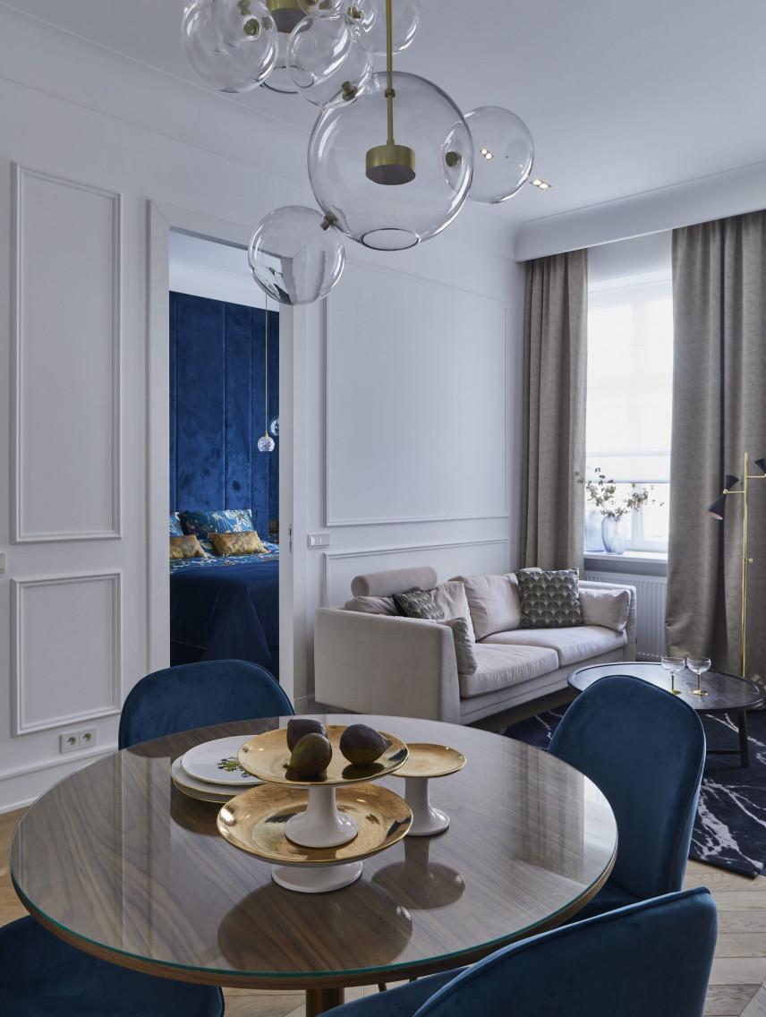 Salon z okrągłym stołem i stylową lampą