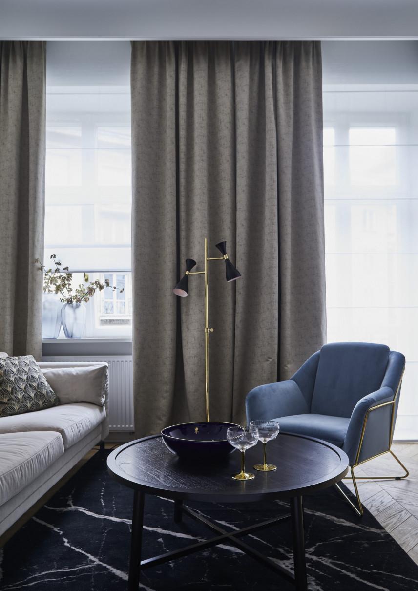 Salon z niebieskim fotelem i szarymi zasłonami