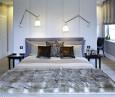 Szara sypialnia z tapicerowaną ścianą