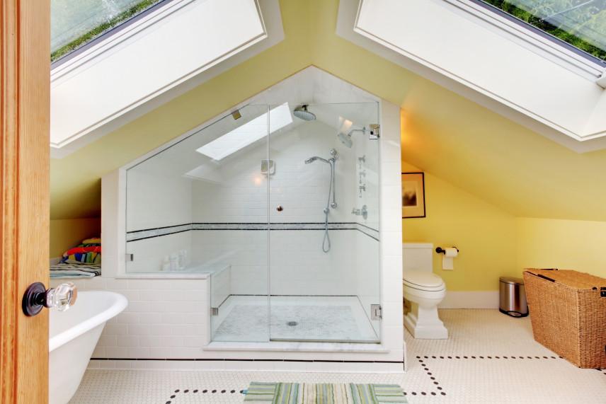 Łazienka na poddaszu z zamknięta kabiną z prysznicem z siedziskiem