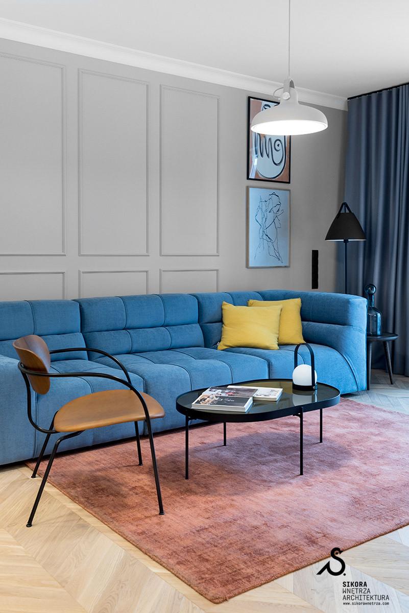 Designerski salon z niebieską kanapą