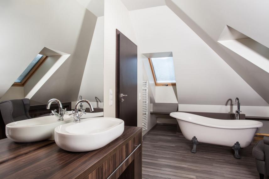 Łazienka na poddaszu z podłogą w kolorze drewna.