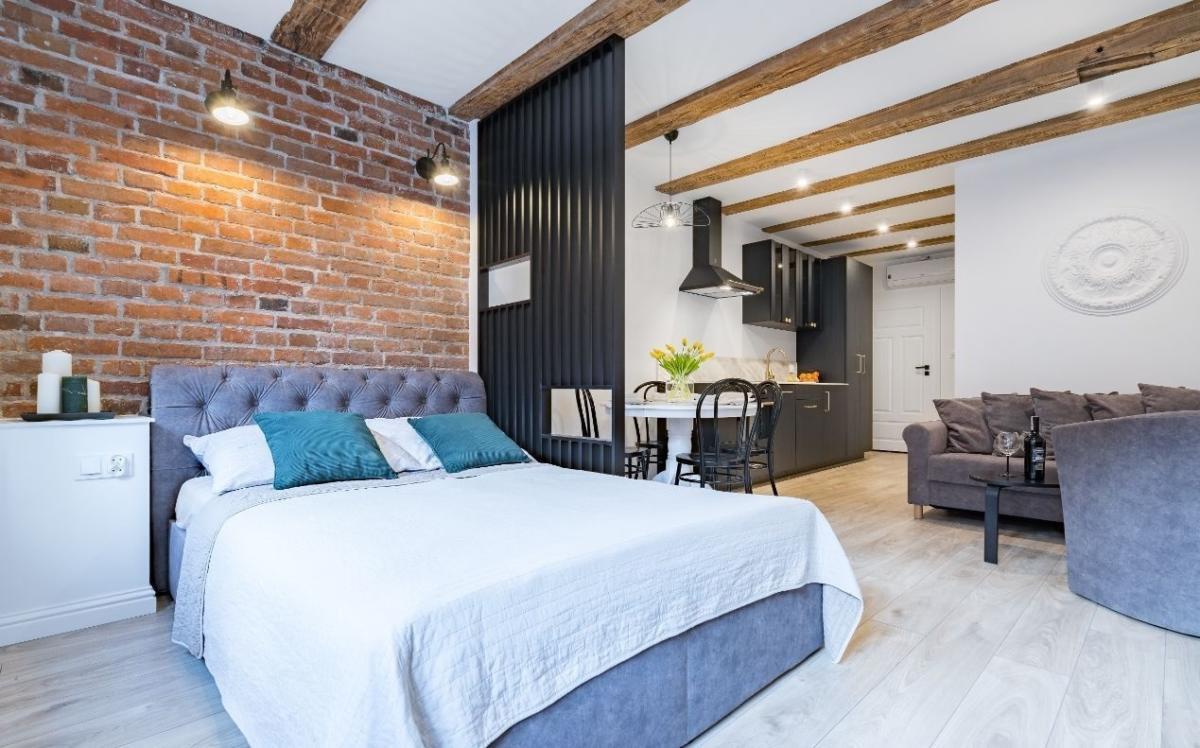 Aranżacja sypialni z czerwoną cegłą na ścianie