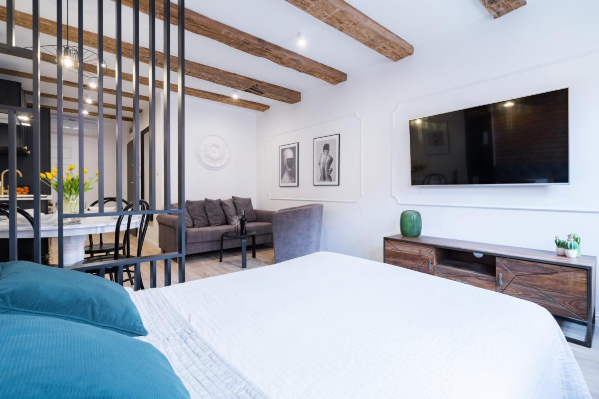 Aranżacja sypialni z drewnianymi elementami na suficie