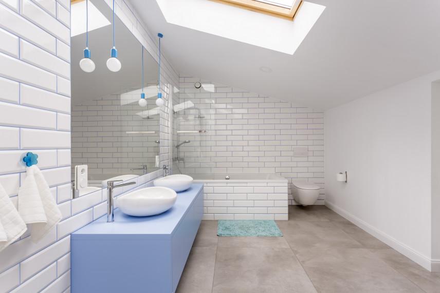 Łazienka na poddaszu z białą cegłą na ścianie