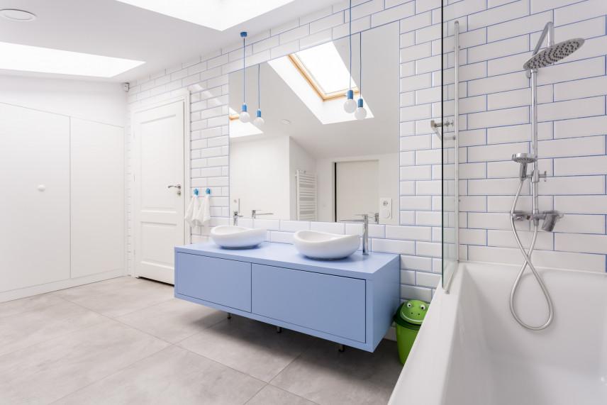 Biała łazienka na poddaszu z niebieską szafką.