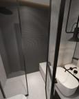 Widok małej łazienki z góry z białym zlewem nablatowym