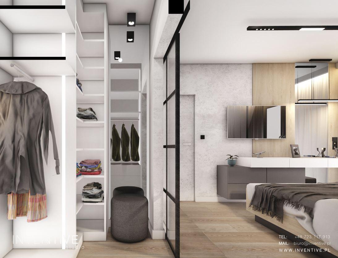 Garderoba w sypialni za przesuwanymi czarnymi, szklanymi drzwiami