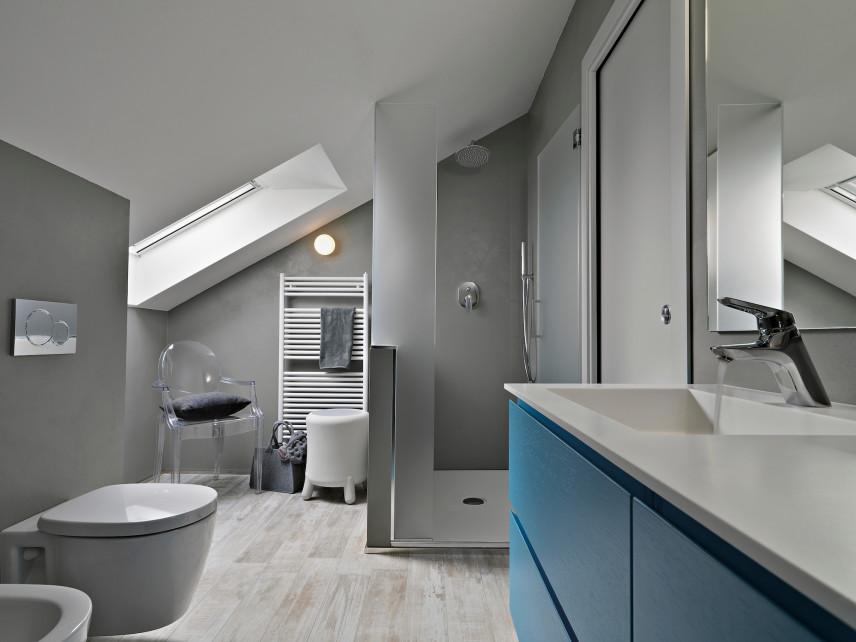 Szara łazienka z niebieska szafka