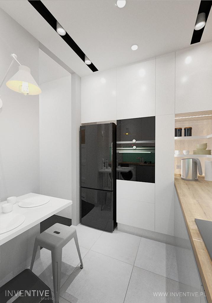 Mała, biała kuchnia z piekarnikiem zamontowanym na wysokości klatki piersiowej