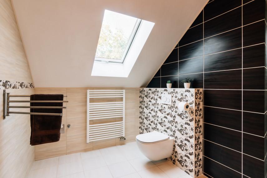Mała łazienka ze ścianą z czarnych kafli