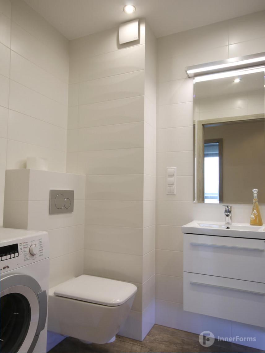Łazienka z białą muszlą wiszącą i poziomymi płytkami
