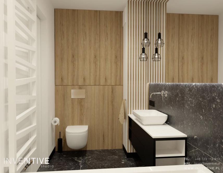 Aranżacja łazienki z czarną szafką stojącą z białym blatem