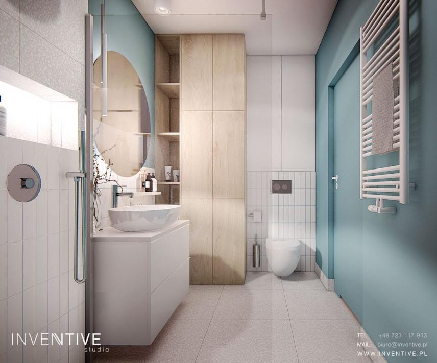Łazienka z turkusowymi ścianami i jasną podłogą