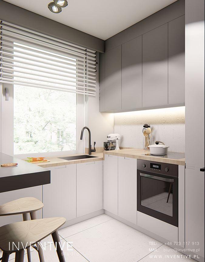 Kuchnia z szaro-białymi frontami i z oknem nad blatem