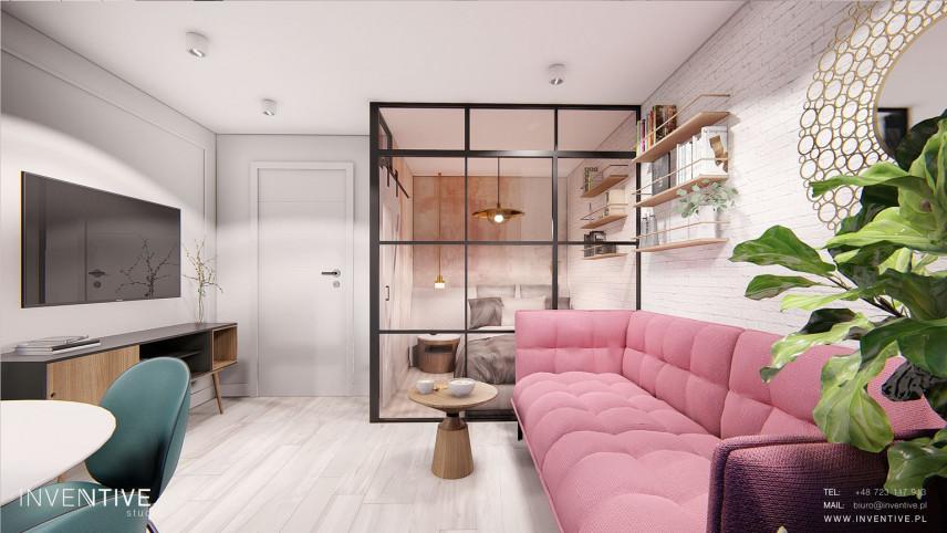 Nowoczesna jadalnia z salonem i z różową sofą