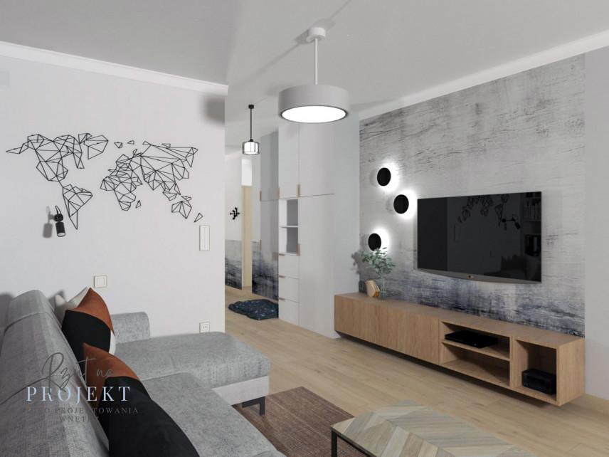 Salon z szarym narożnikiem i drewnianą szafką stojącą pod telewizorem