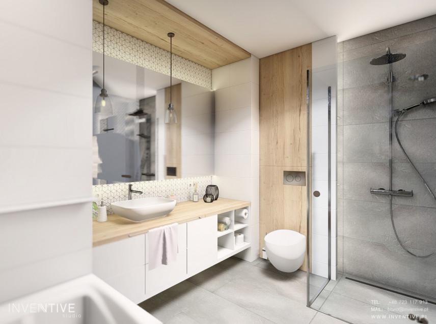 Przestrzenna i funkcjonalna łazienka z prysznicem i szarą podłogą