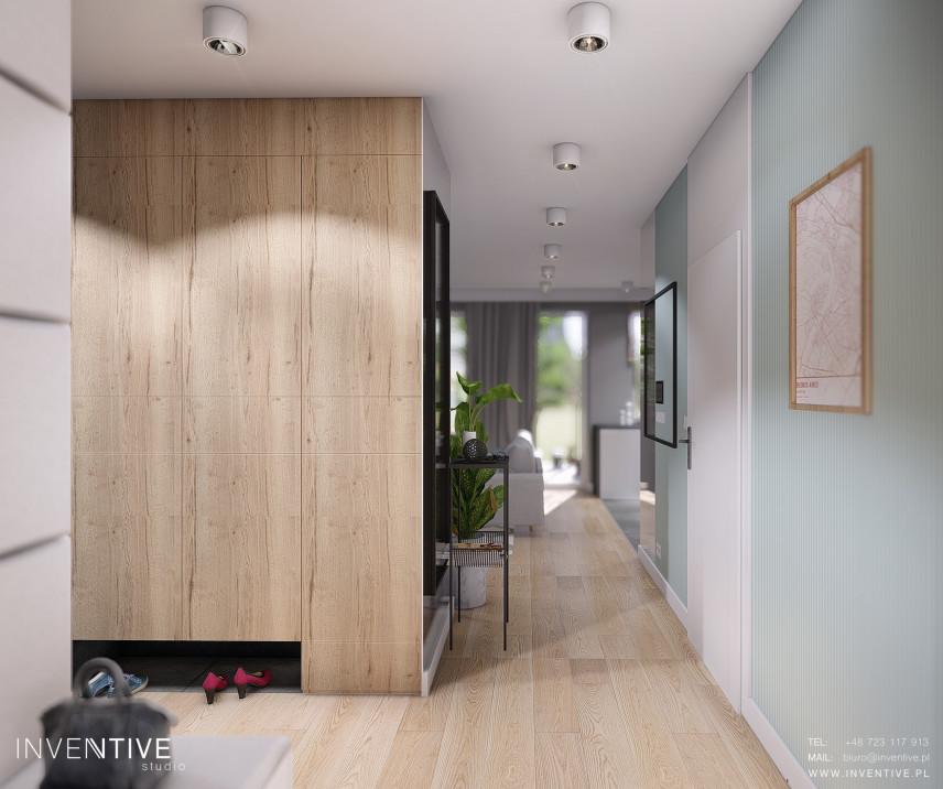 Przedpokój z dużą drewnianą szafą w zabudowie