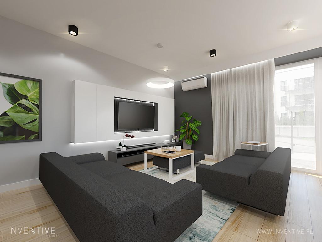 Aranżacja salonu z dużymi sofami i telewizorem na ścianie