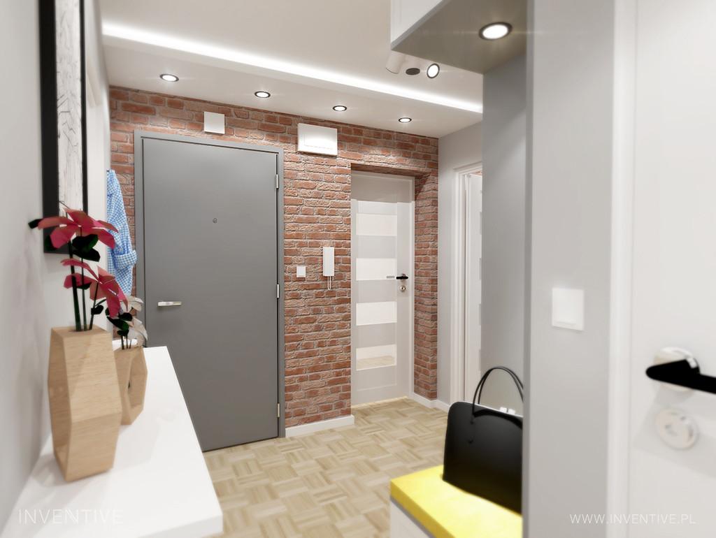 Aranżacja małego przedpokoju z cegłą  na ścianie