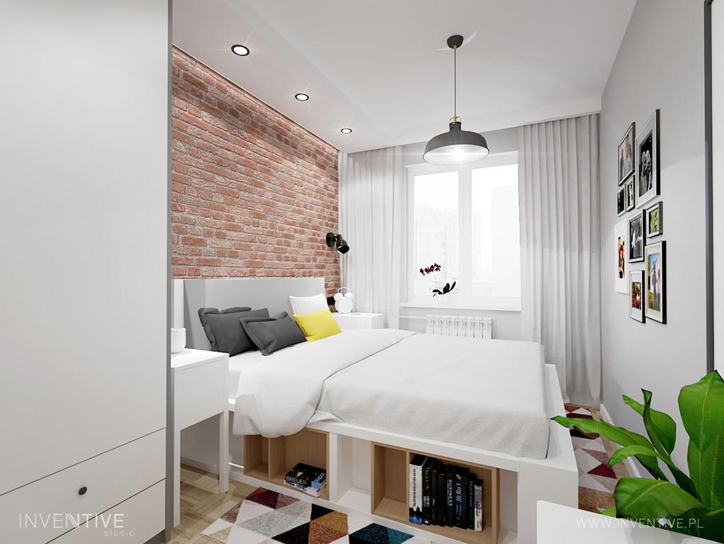 Mała sypialnia z czerwoną cegłą na ścianie i z białym łóżkiem kontynentalnym