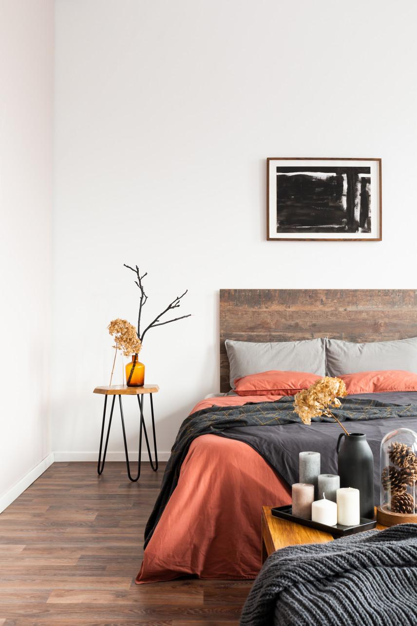 Sypialnia z drewnianym łóżkiem i obrazem