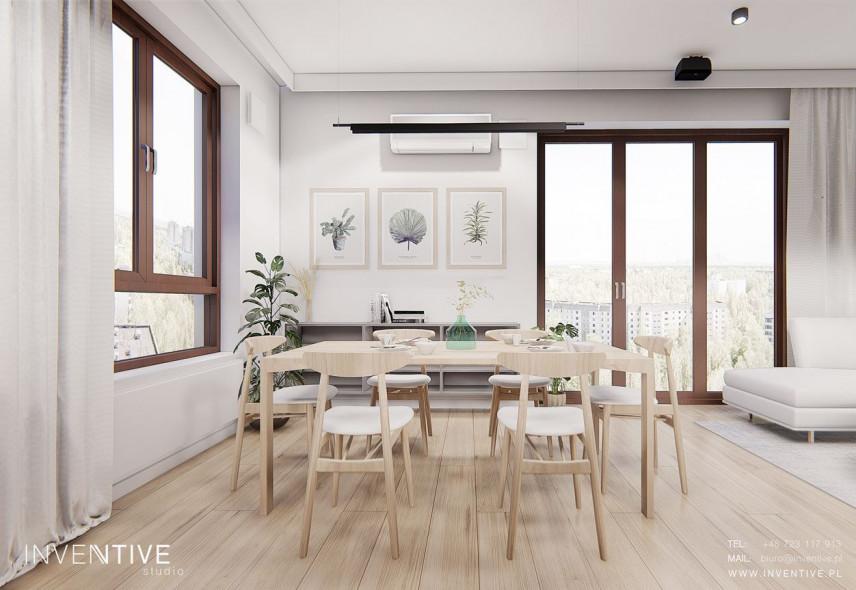 Jadalnia z drewnianym stołem i z obrazami z motywem floralnym na ścianie