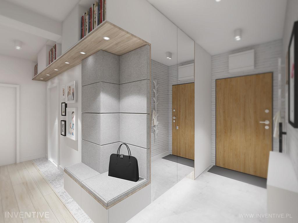 Przedpokój w jasnych kolorach z półką zamontowaną pod sufitem