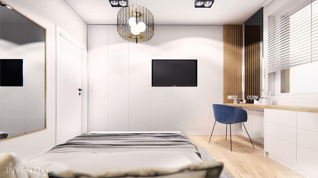 Sypialnia z biurkiem i telewizorem na ścianie