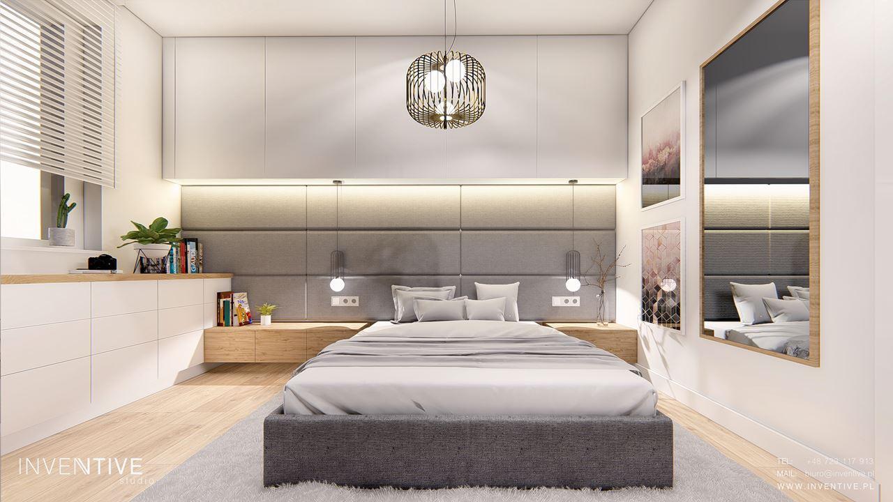 Sypialnia z meblami w zabudowie i tapicerowaną ścianą w kolorze szarym