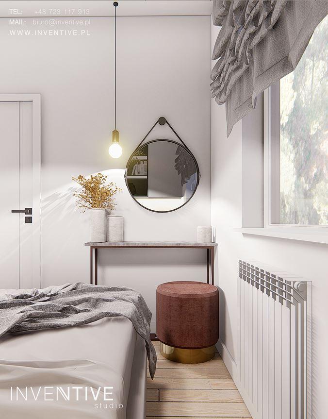 Sypialnia z białymi ścianami i szarą roletą rzymską