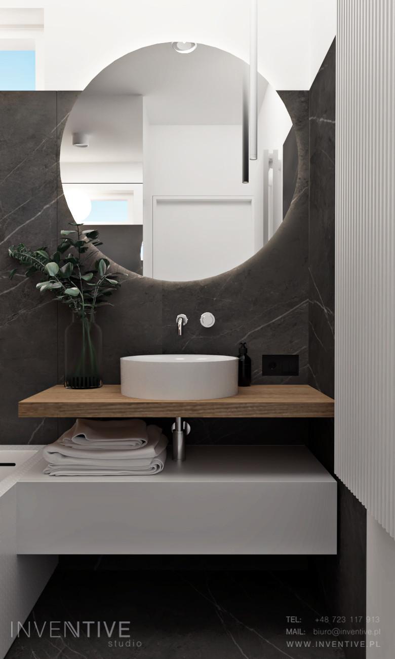 Łazienka z czarnymi płytkami gresowymi na ścianie i podłodze