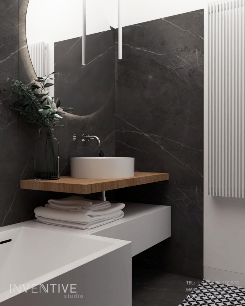 Łazienka z okrągłym lustrem i białym zlewem nablatowym