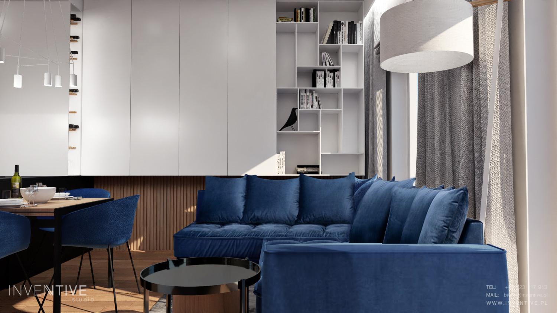 Salon z białymi meblami w zabudowie z granatową sofą