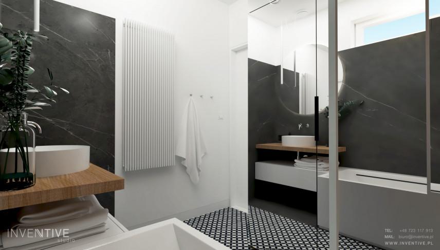 Łazienka z czarnymi płytkami na ścianie i białym kaloryferem