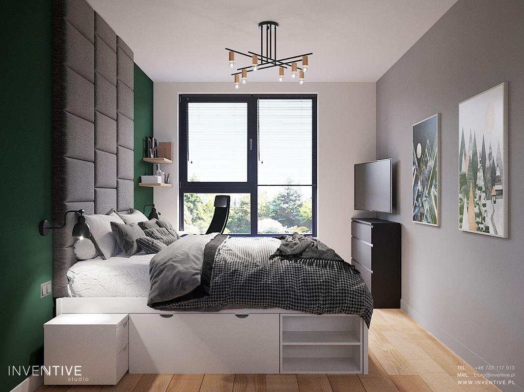 Sypialnia z białym łóżkiem kontynentalnym i szarą ścianą tapicerowaną