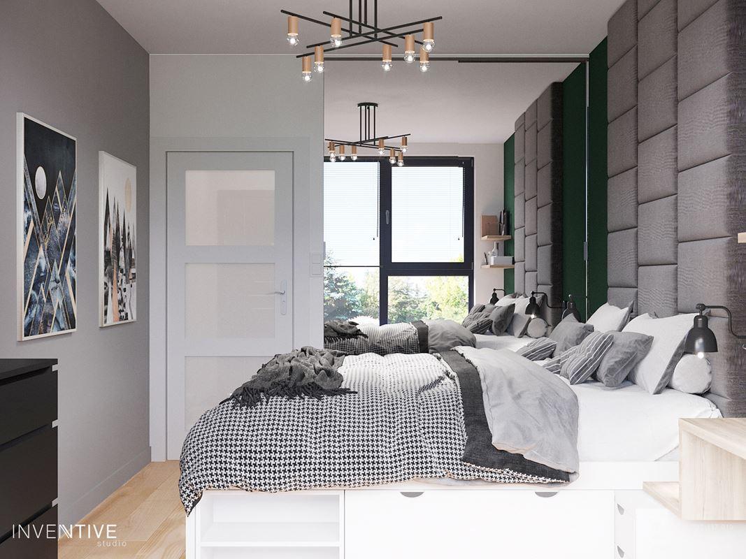 Sypialnia z tapicerowanym kawałkiem ściany za łóżkiem kontynentalnym