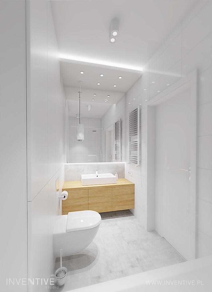 Minimalizm w łazience z drewnianą szafką wiszącą