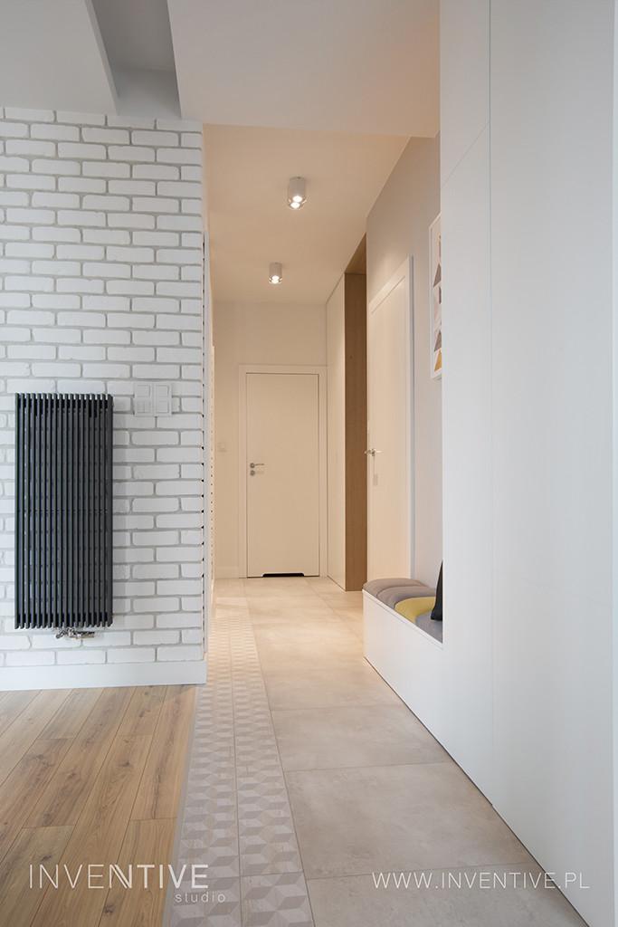 Aranżacja wąskiego korytarza z białą cegłą na ścianie